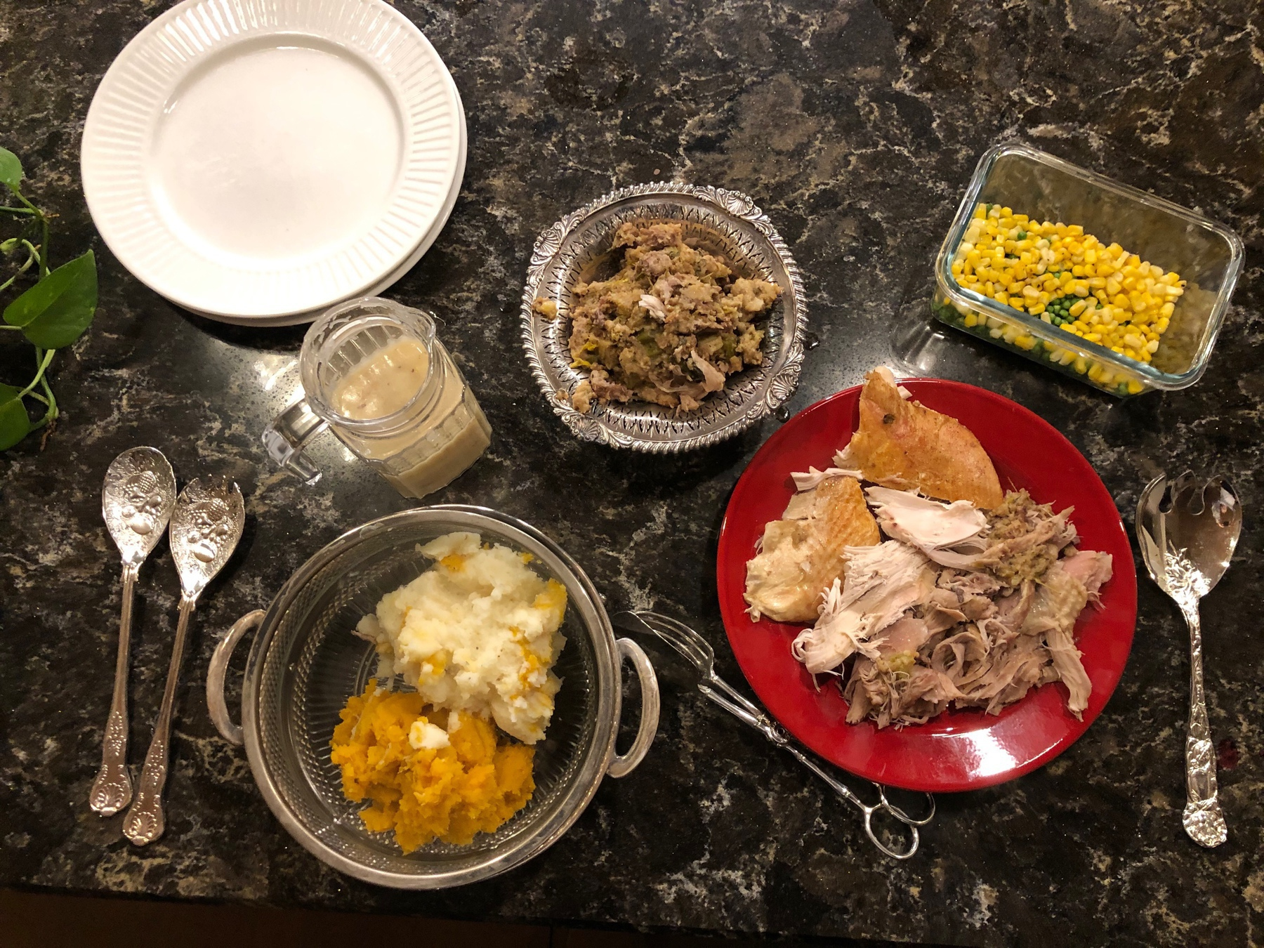 bowls and plates of turkey, dressing, sweet and white potatoes, corn and peas