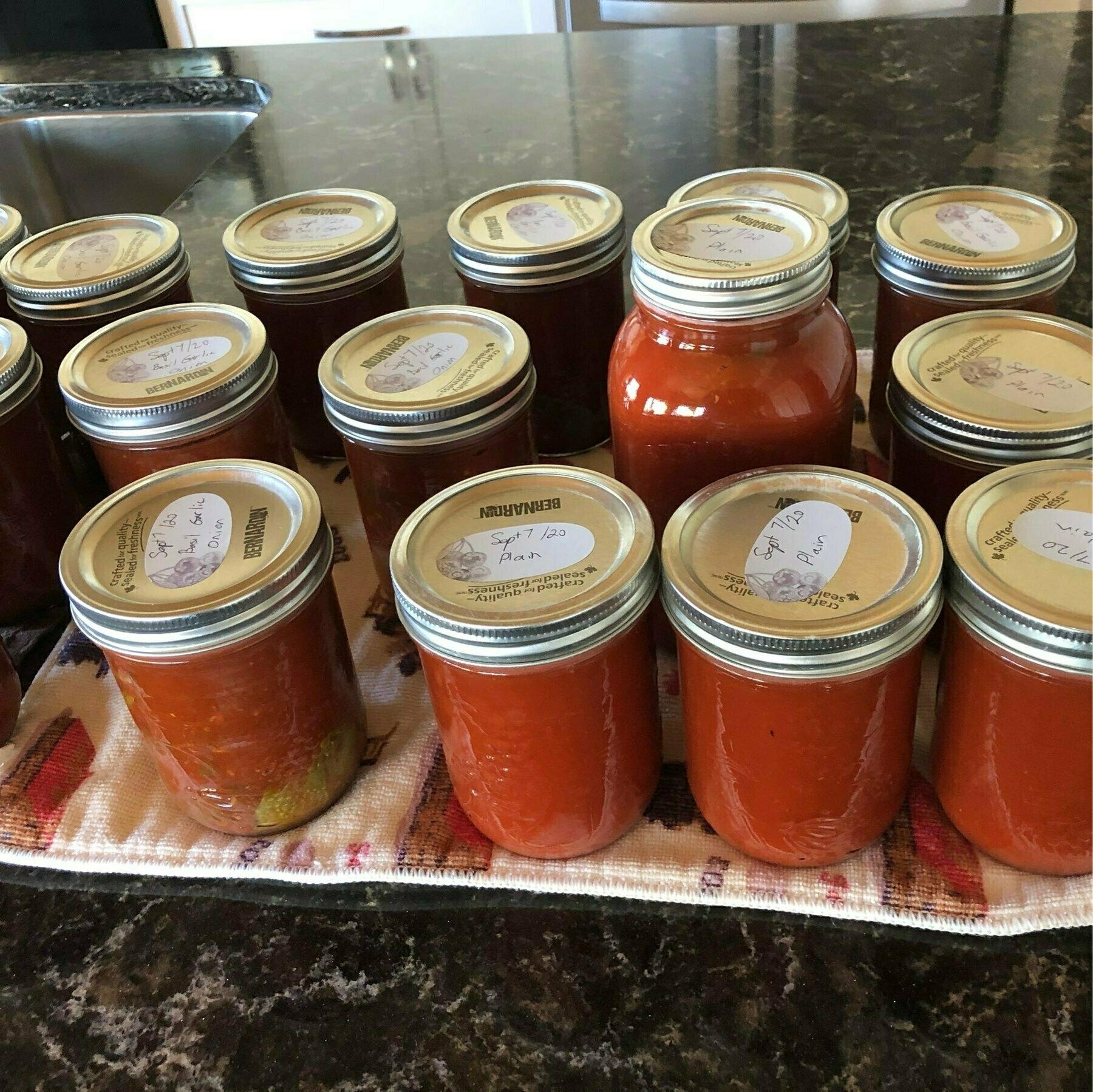 multiple jars of tomato sauce sitting on a dark countertop