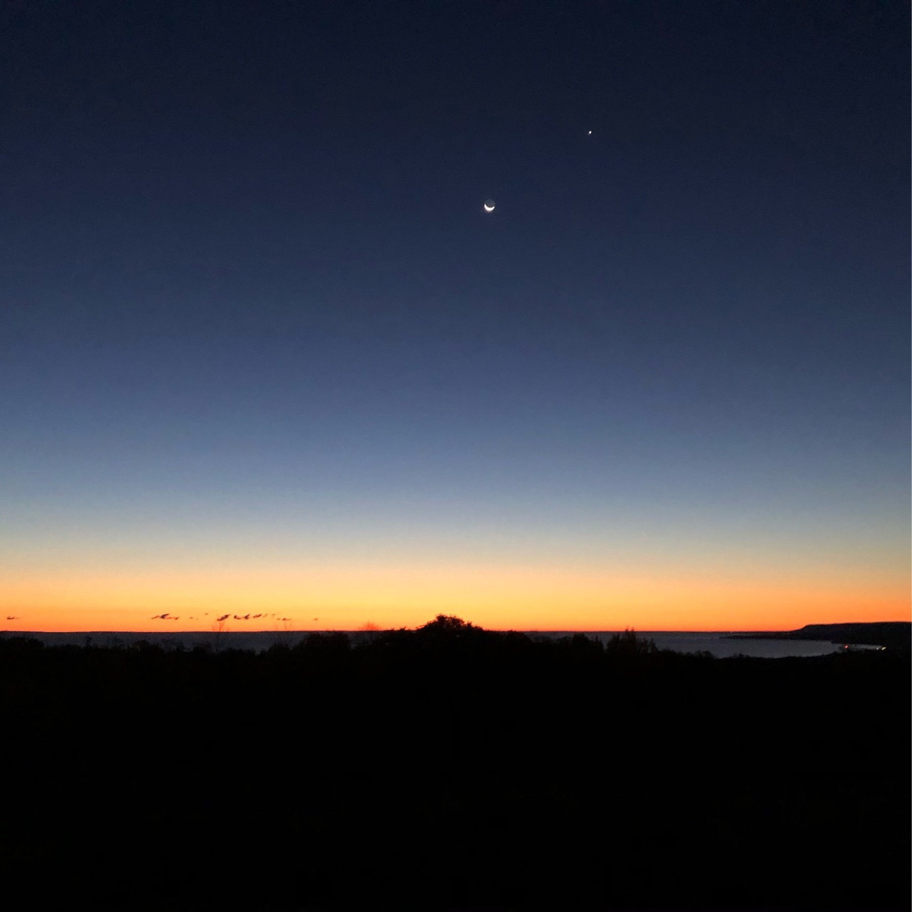 red sunrise over dark land and water. a crescent moon and bright star visible in the upper right
