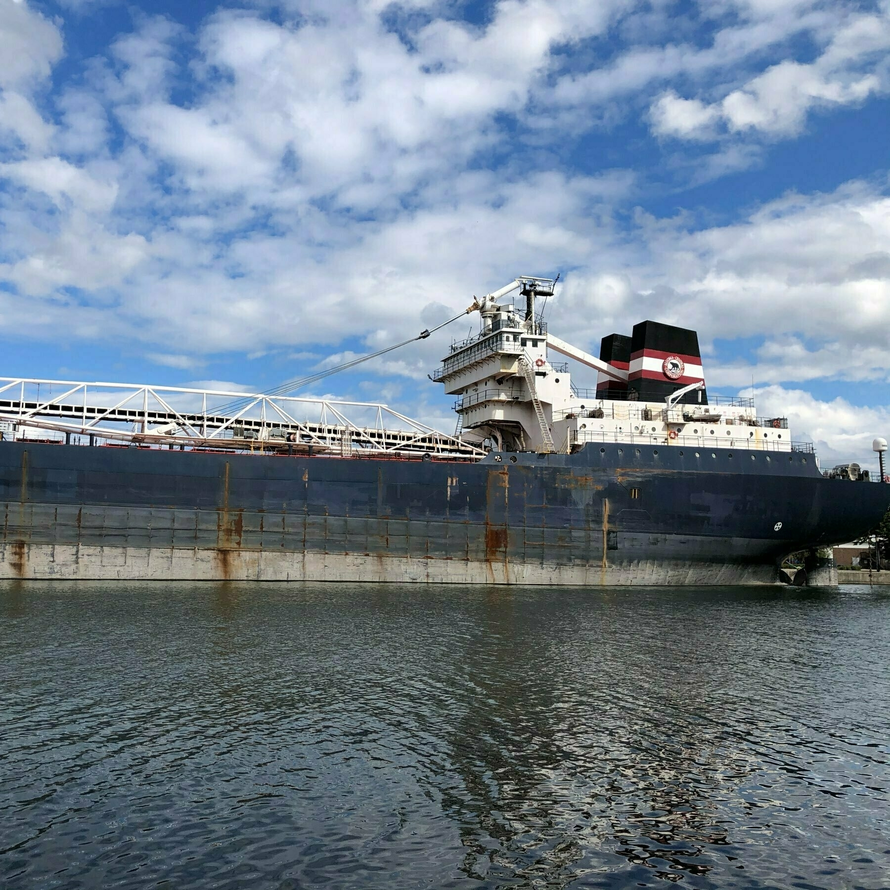the back third of a great lakes freighter moored in a harbour. vertical and horizontal lines delineate steel panels on its black side
