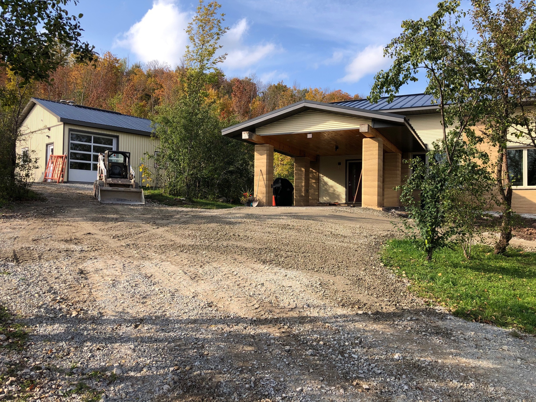 fresh gravel on a driveway leading into a carport. a Bobcat loader and a second building wkyh a garage door are in the background