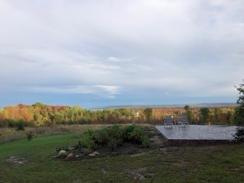 two blue chairs and a small table on a grey concrete patio. Georgian Bay is in the background as are many coloured leaves. Some tomato vines are visible on the left side