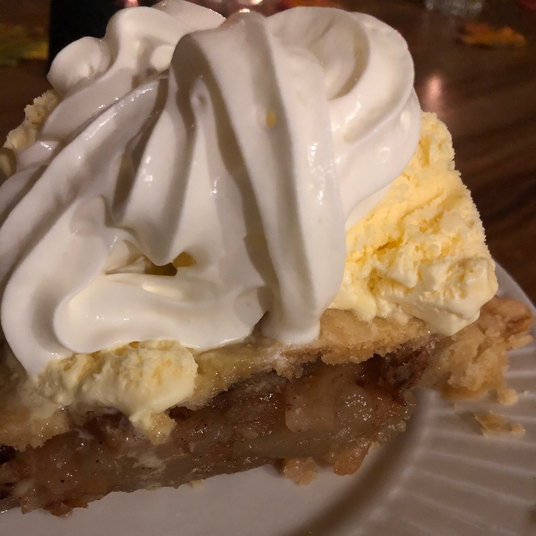 a slice of apple pie with whopped cream on top