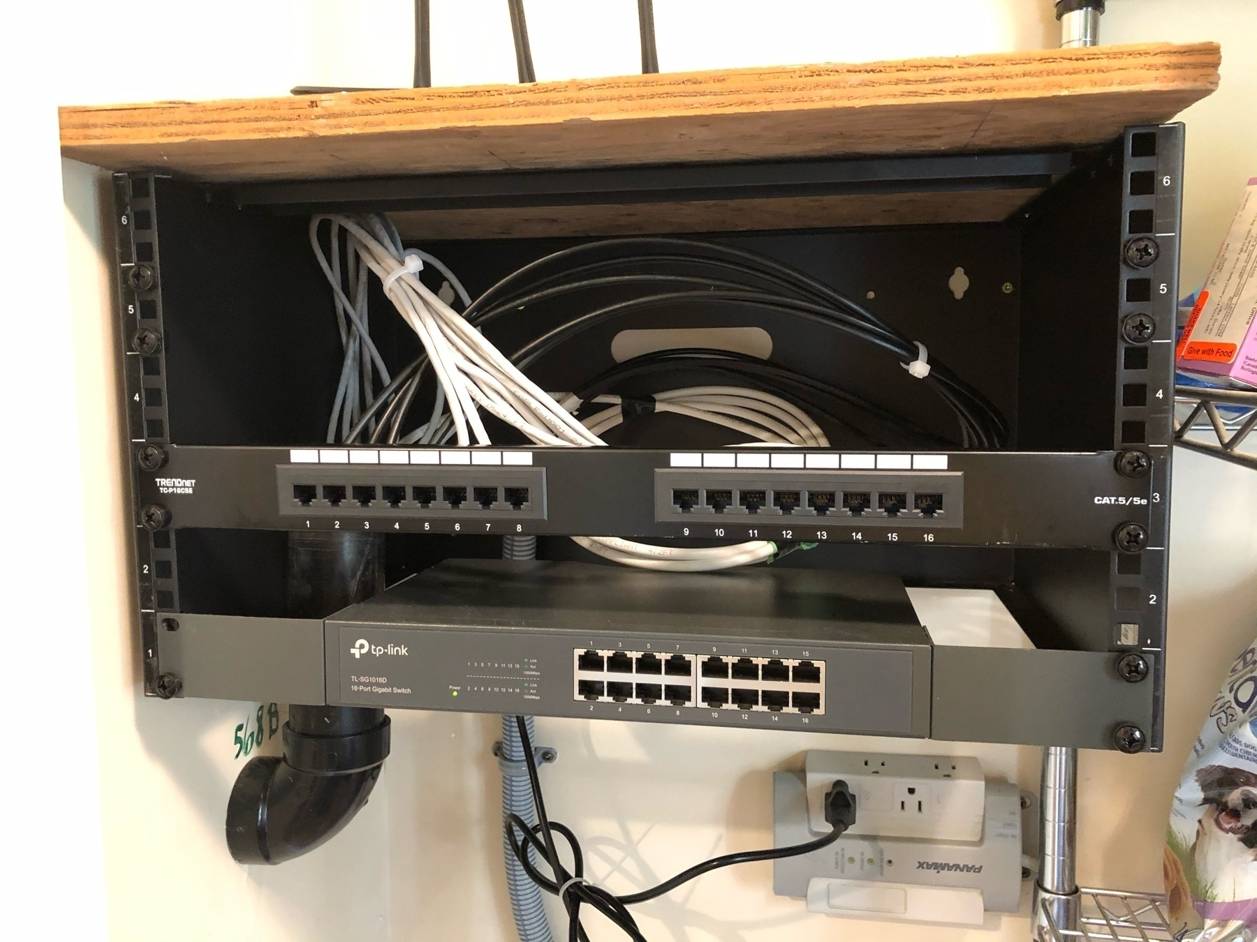 16 port patch panel installed over a switch with multiple cables bundled behind