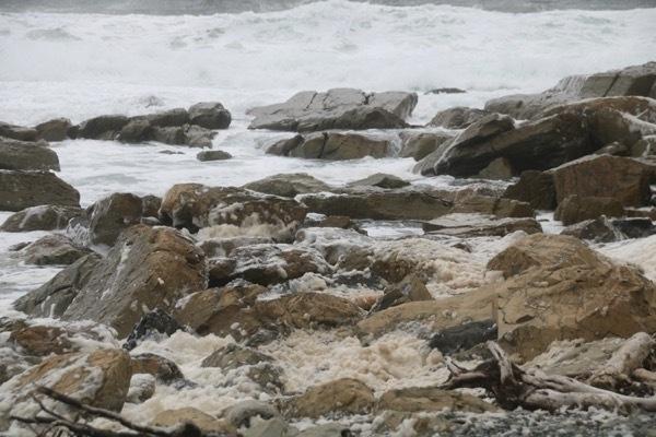 foam on water mixing around rocks