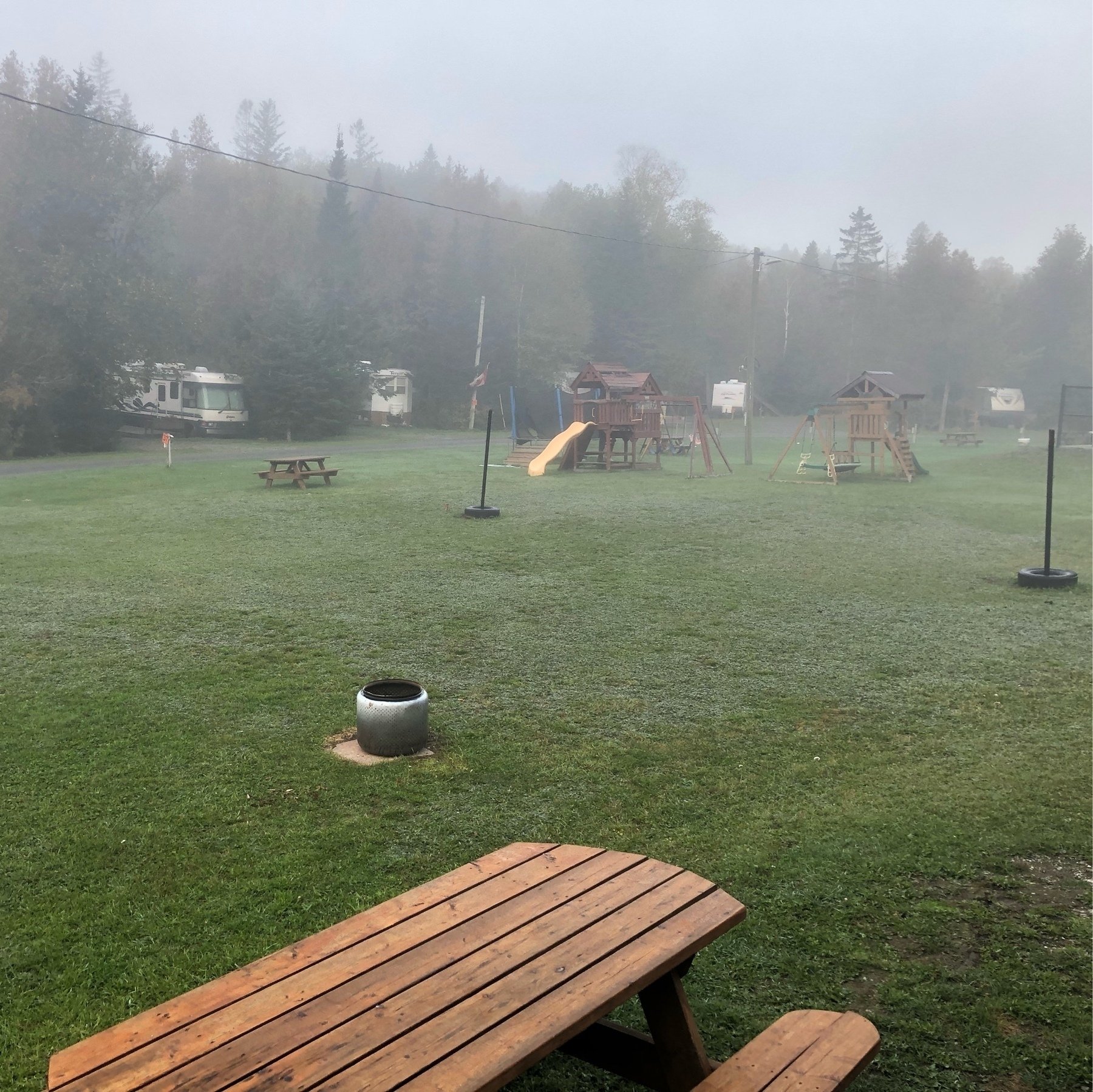 a picnic table on frost-covered grass. fog in the air. kids playground equipment in the background