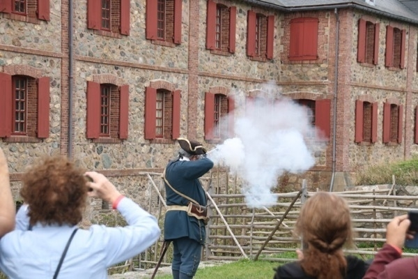 smoke from the barrel of a musket. tourists in front taking photos