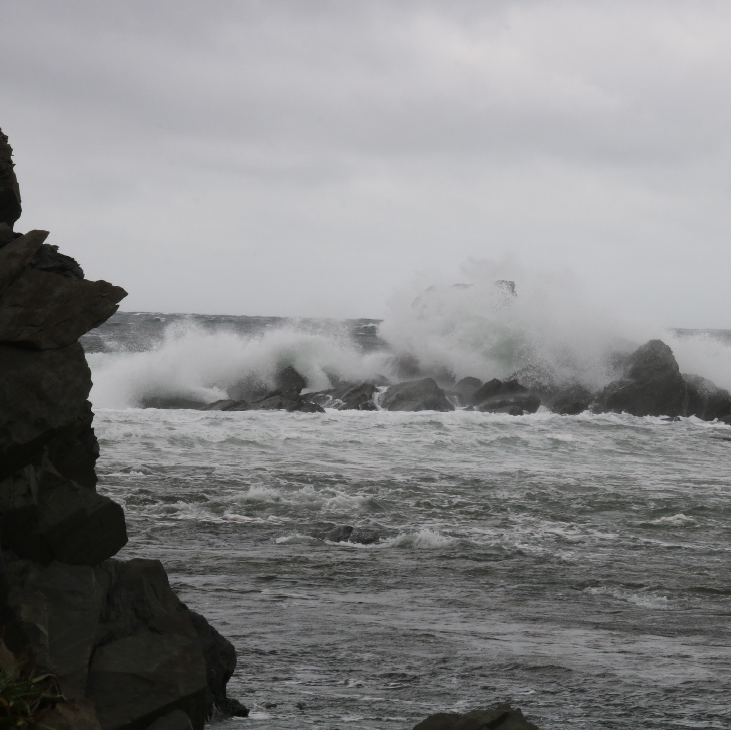 waves crashing over rocks. there is a rock wall on the left side