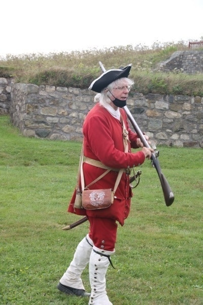 soldier in costume explaining the operation of a musket