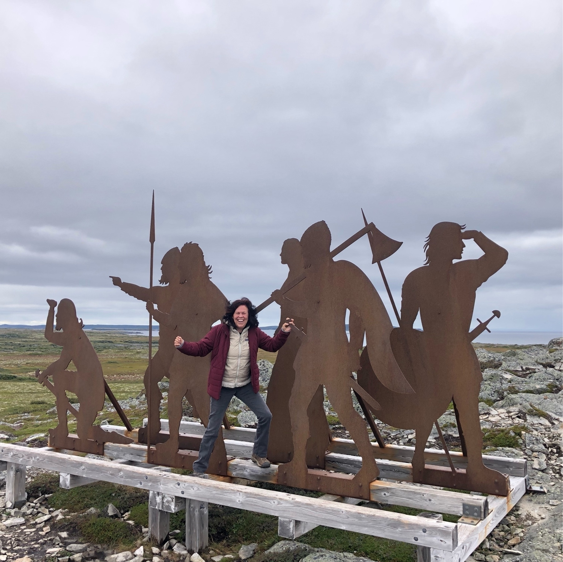 a woman in the middle of a rusty scupture of various explorers