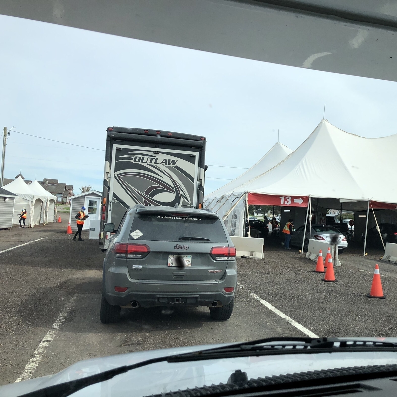 motor home pulling a car. large tents with automobiles entering. concrete barriers
