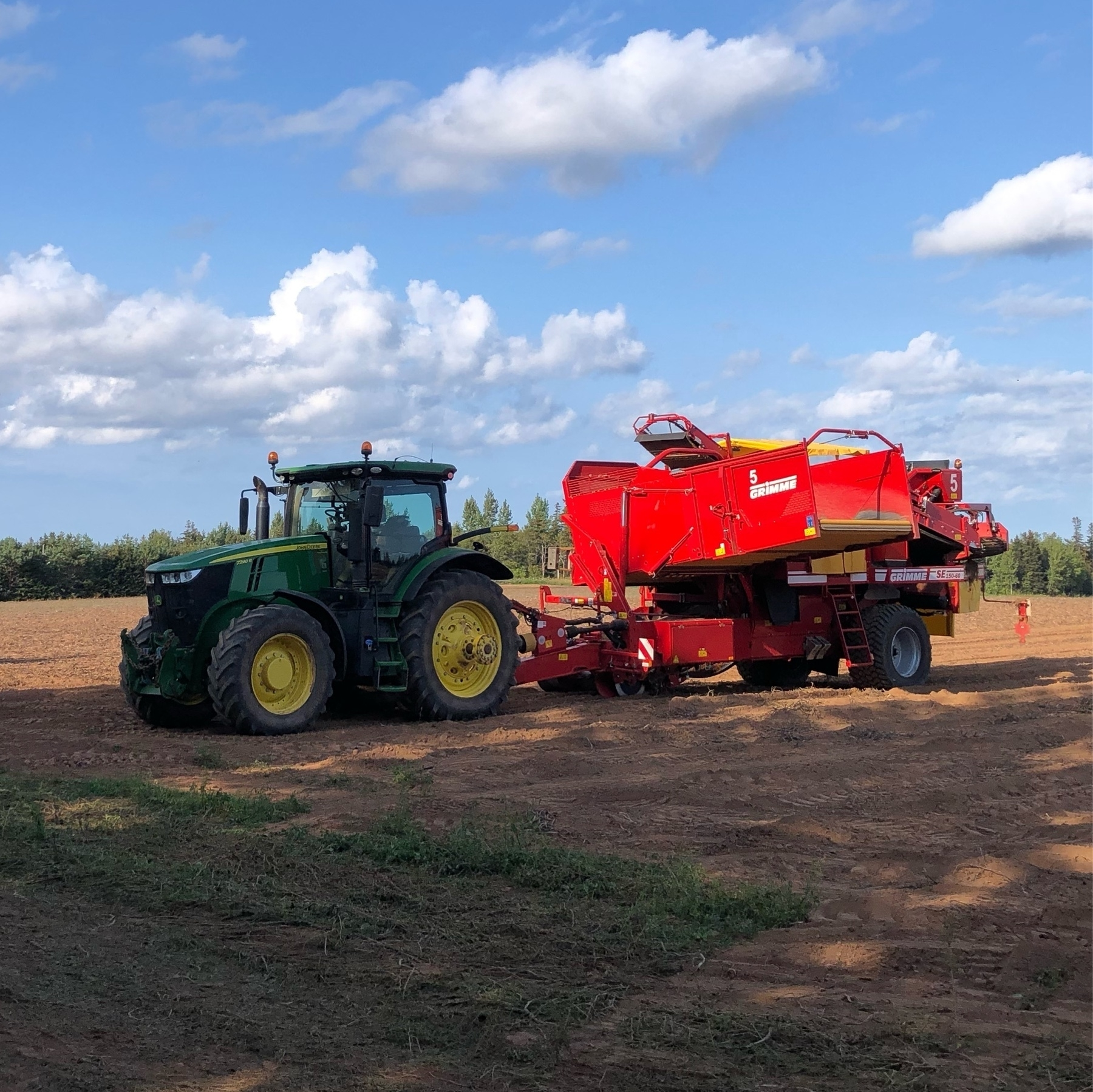 a large tractor pulling a red implement. they are in a field lf red soil. a few clouds in the sky